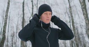 Un hombre joven en una sacudida de la mañana sostiene los auriculares en sus manos y los inserta en sus oídos antes de correr en  metrajes