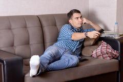 Un hombre joven en vaqueros, con un teledirigido para el aburrimiento de la TV en la cara cambia el canal fotografía de archivo libre de regalías