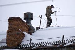 Un hombre joven en vestidos negros se está colocando en un tejado rojo y está limpiando la chimenea con un cepillo del metal en u foto de archivo