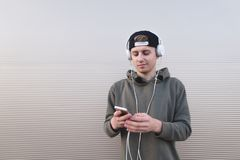 Un hombre joven escucha la música en los auriculares y mira su smartphone en el fondo de una pared ligera Fotos de archivo