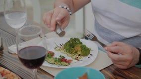 Un hombre joven está almorzando con una ensalada con las verduras en un restaurante en la terraza abierta Alimento sano metrajes