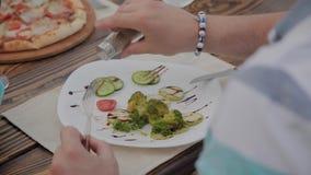 Un hombre joven está almorzando con una ensalada con las verduras en un restaurante en la terraza abierta Alimento sano almacen de video