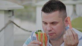 Un hombre joven está almorzando con una ensalada con las verduras en un restaurante en la terraza abierta Alimento sano almacen de metraje de vídeo