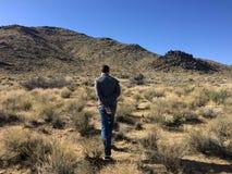 Un hombre joven está caminando en el desierto de Arizona al mediodía Fotos de archivo libres de regalías