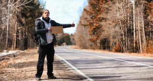 Un hombre joven está haciendo autostop alrededor del país El hombre está intentando fotos de archivo
