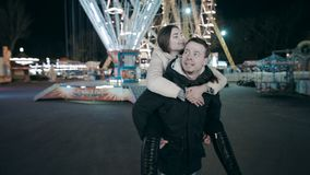 Un hombre joven está llevando a una mujer hermosa en el suyo detrás Fecha en el parque de atracciones metrajes
