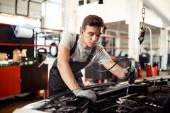 Un hombre joven está ocupado con la comprobación de un motor de automóvil: reparación y mantenimiento del coche foto de archivo libre de regalías