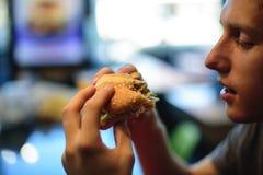 Un hombre joven está a punto de morder una hamburguesa apetitosa Fotos de archivo