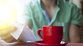 Un hombre joven examina la cuenta en un café en una mañana soleada del verano fotos de archivo