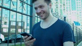 Un hombre joven feliz está caminando abajo de la calle con un smartphone en sus manos y sonrisa Va a lo largo de la cerca con almacen de metraje de vídeo