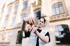 Un hombre joven hace clic su finger en la pantalla de su teléfono para tomar una foto Un hombre joven elegante hace un sephi Imagenes de archivo