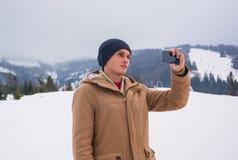 Un hombre joven hace el selfie en el teléfono Paisaje de la montaña en Tran fotos de archivo