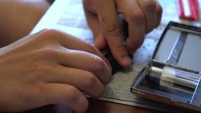 Un hombre joven hace un papel de relleno del cigarrillo hecho a mano con el tabaco destrozado usando una prensa de batir