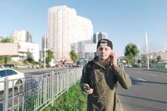 Un hombre joven hermoso con una mochila y los auriculares en sus oídos disfruta de música mientras que camina alrededor de la ciu Imágenes de archivo libres de regalías
