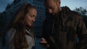 Un hombre joven hermoso con una mujer que usa un smartphone está buscando una calle en la ciudad Pares felices en la noche en almacen de metraje de vídeo
