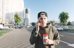 Un hombre joven hermoso con una taza de café en sus manos habla por el teléfono mientras que camina alrededor de la ciudad Imagen de archivo