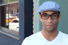 Un hombre joven hermoso en la ropa llana que lleva el sombrero y los vidrios fotografía de archivo libre de regalías