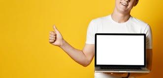 Un hombre joven hermoso que sostiene y que muestra la pantalla de un ordenador port?til fotografía de archivo