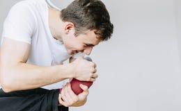 Un hombre joven huele sus calcetines, llevando a cabo su pie en su mano Fondo gris aislado fotos de archivo