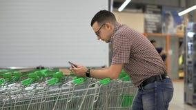 Un hombre joven imprime un mensaje en la pantalla de su smartphone, inclinándose en el carro de la compra en el supermercado usin almacen de video