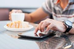 Un hombre joven lee las noticias en el dispositivo Foto de archivo libre de regalías