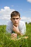Un hombre joven lee un libro, mintiendo en una hierba. Fotografía de archivo