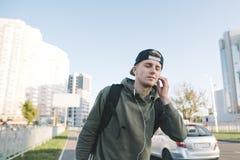 Un hombre joven lindo y elegante que camina abajo de la calle y que disfruta de la música que juega los auriculares en el fondo d Imagen de archivo