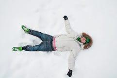 Un hombre joven, mintiendo en la nieve Fotografía de archivo libre de regalías