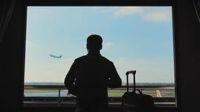 Un hombre joven mira el aeroplano sacar de la ventana de su habitación almacen de metraje de vídeo