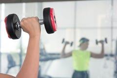 Un hombre joven mira el brazo muscle la situación delante del espejo Foto de archivo