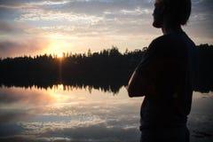 Un hombre joven mira la puesta del sol sobre la ensenada de Crocket en Stonington, Maine Imagen de archivo libre de regalías