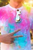 Un hombre joven muestra el símbolo de la paz y de la amistad Fest de Holi Imagenes de archivo