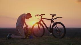 Un hombre joven pone cosas en una mochila Se sienta por la bici en la puesta del sol almacen de metraje de vídeo