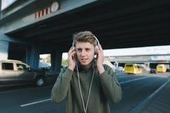 Un hombre joven positivo está escuchando la música en la calle en auriculares en el fondo de la arquitectura Estafa de la forma d Fotos de archivo