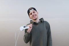 Un hombre joven positivo se coloca cerca de una pared ligera, de los auriculares de los controles y de las sonrisas Imágenes de archivo libres de regalías