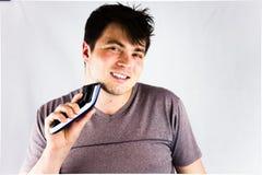 Un hombre joven que afeita su barbilla con una máquina de afeitar eléctrica Adolescente que sostiene su condensador de ajuste elé Fotografía de archivo