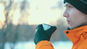Un hombre joven que bebe una bebida caliente de un termo en un invierno parquea Nevadas grandes El hombre en una chaqueta anaranj almacen de video