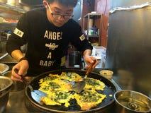 Un hombre joven que cocina ostras en estilo local en un restaurante en la ciudad de Xiamen, China Fotos de archivo