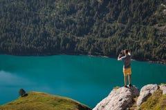 Un hombre joven que enmarca un árbol con sus manos Ritom del lago como fondo imagenes de archivo