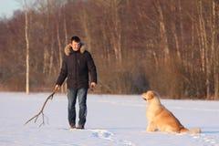 Un hombre joven que entrena a su golden retriever del perro Imágenes de archivo libres de regalías