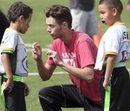 Un hombre joven que entrena un equipo de fútbol de la bandera Foto de archivo libre de regalías
