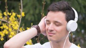Un hombre joven que escucha la música por los auriculares blancos en el parque - jardín botánico durante tiempo de primavera prec Foto de archivo