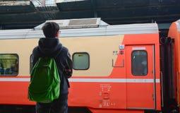 Un hombre joven que espera un tren en la plataforma Imágenes de archivo libres de regalías