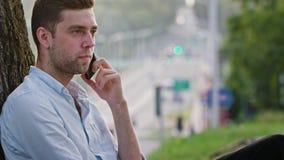 Un hombre joven que habla en el teléfono debajo de un árbol almacen de metraje de vídeo