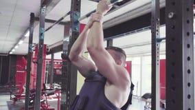 Un hombre joven que hace tirón sube en el gimnasio almacen de video