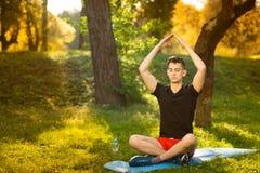 Un hombre joven que hace yoga en el parque verde concepto de una forma de vida sana fotografía de archivo