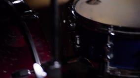 Un hombre joven que juega los tambores en la oscuridad Piernas del primer 4K metrajes