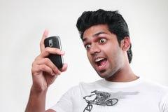 Un hombre joven que mira su móvil con la expresión del exitement Imagenes de archivo