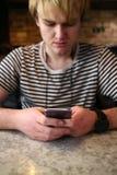 Un hombre joven que mira su teléfono la tabla Fotos de archivo