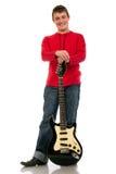 Un hombre joven que se coloca con una guitarra eléctrica en un fondo blanco Imágenes de archivo libres de regalías